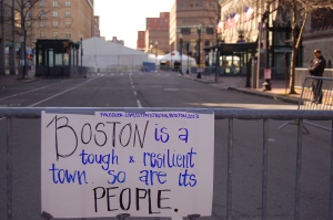 A handwritten poster hangs from a street barricade near Copley Square.