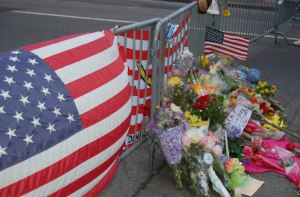 American flags and bouquets adorn the street barricade at the intersection of Berkeley and Boylston Streets in Boston's Back Bay community.